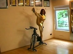 Acrobatic floozy reveals jugs, stripping off her tight gold suit