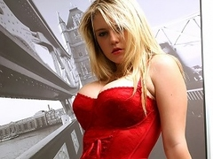 A blonde wholesale with bg tits and dressed in a tight corset is standing...